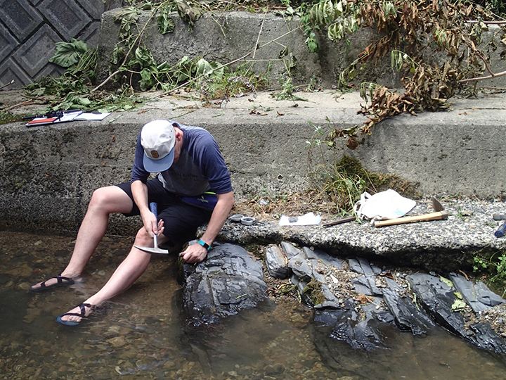 man taking sample from rock in river
