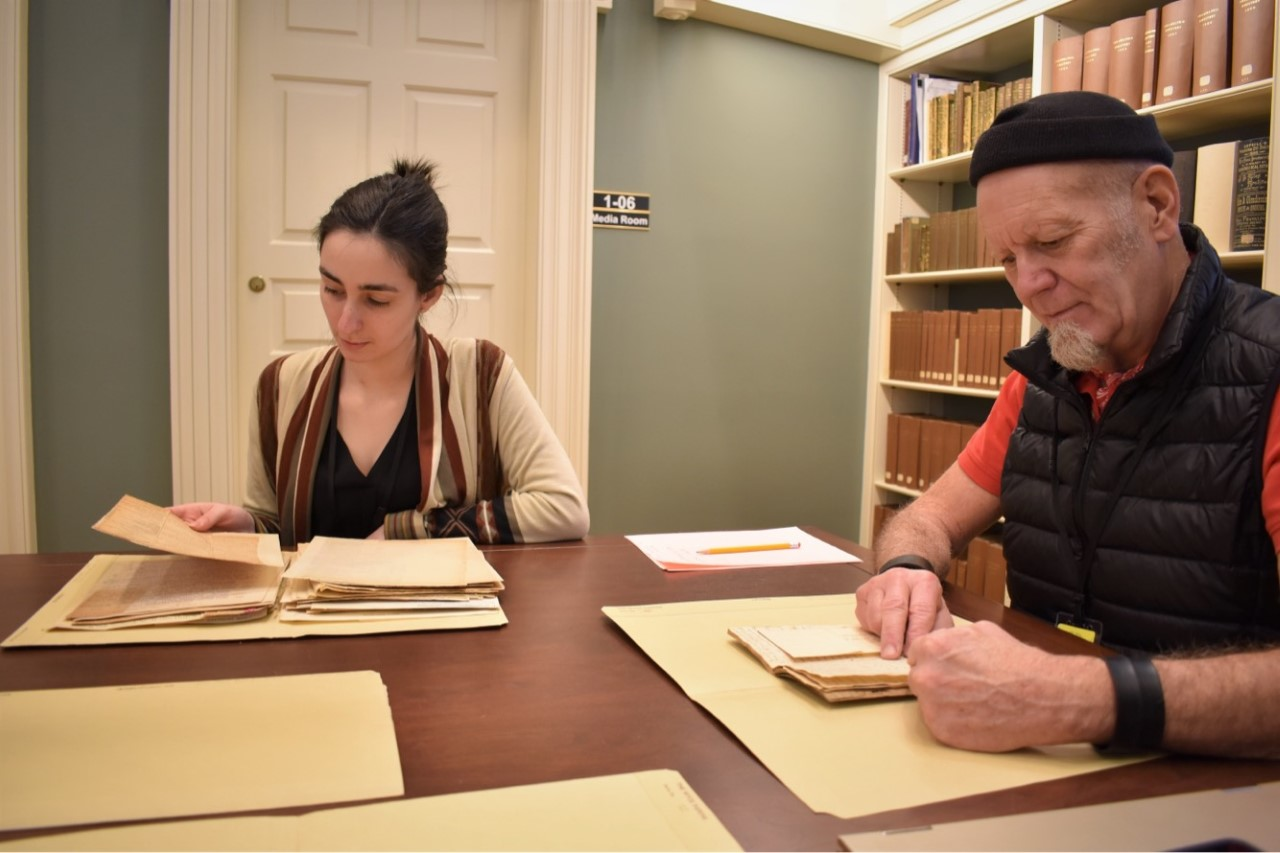 two people looking at documents in library