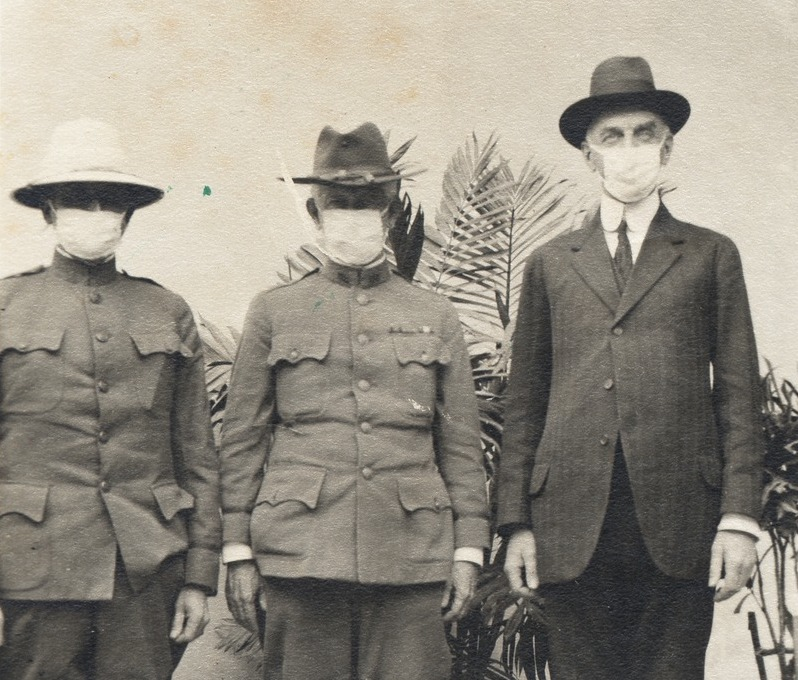 black and white photo of three men wearing surgical masks
