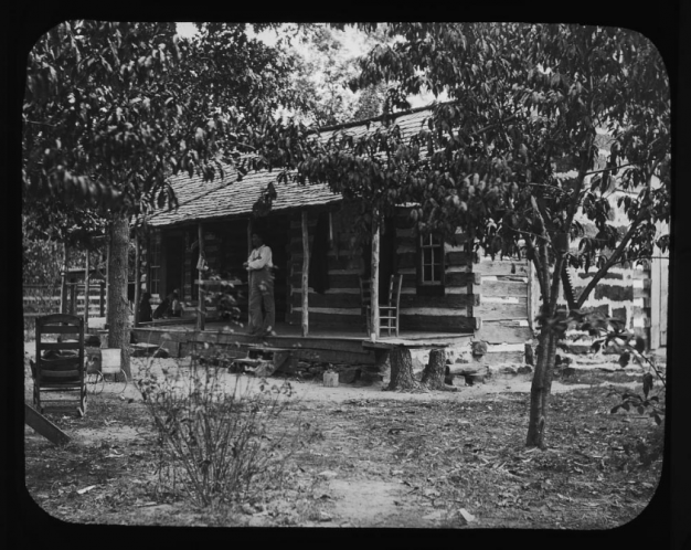 black and white photo of man on porch of log cabin