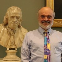 man next to bust of Franklin
