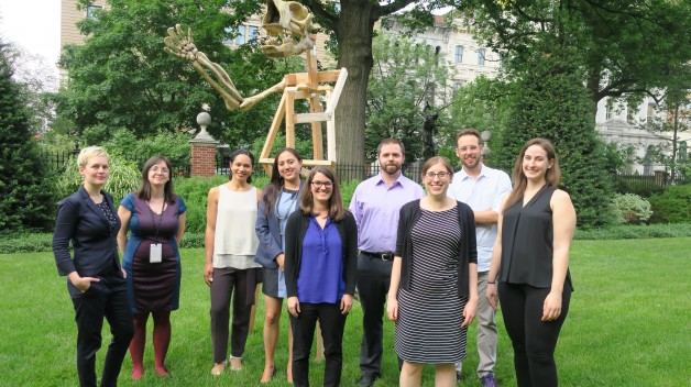group standing in garden in front of giant sloth skeleton sculpture