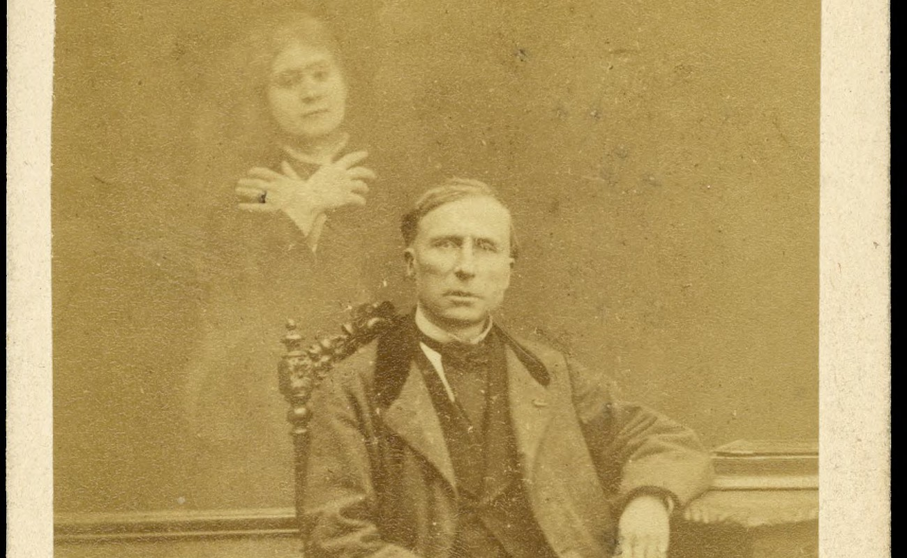 Photograph of seated man with spirit woman behind him