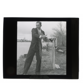 Black-and-white glass lantern slide of a Houma man wearing a suit and spreading out a fishing net.