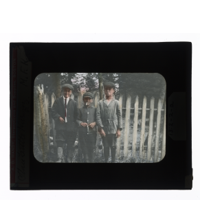 Hand-colored glass lantern slide of three Huron-Wendat boys, in the attire of the day, smoking by a fence, Ontario, Canada.