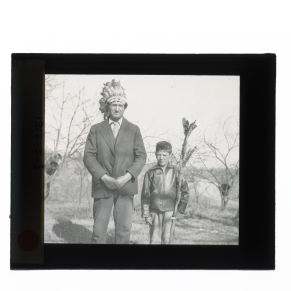 Black-and-white glass lantern slide man wearing head dress standing next to boy with spear.