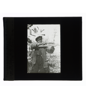 Black-and-white glass lantern slide of an Innu boy holding a crossbow at Lake St. John, Quebec.