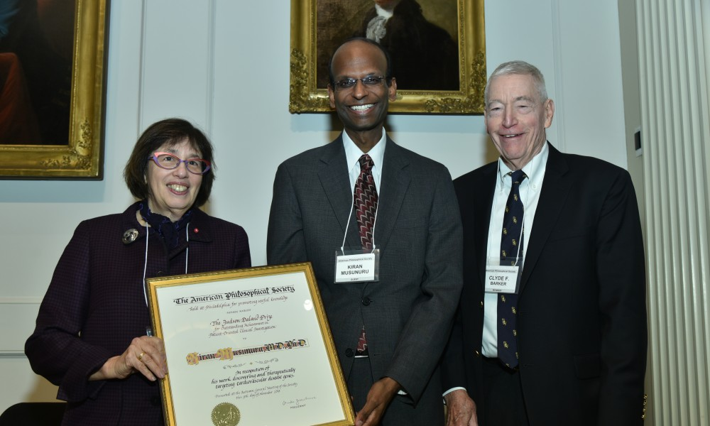 two men and one woman standing with certificate