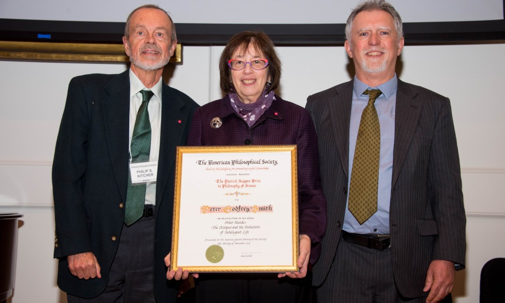 Linda Greenhouse holds the Suppes Prize certificate, standing between Phillip Kitcher and Peter Godfrey-Smith