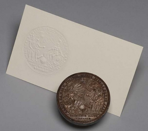 circular engraved metal seal and white card with seal impression