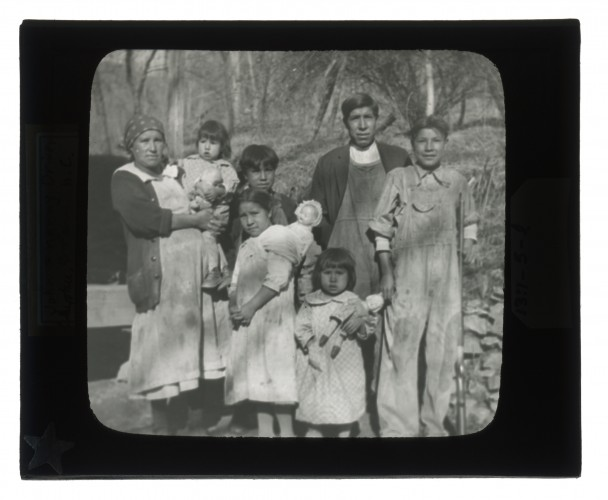 Black-and-white glass lantern slide of John and Nanny Driver and family standing outside.