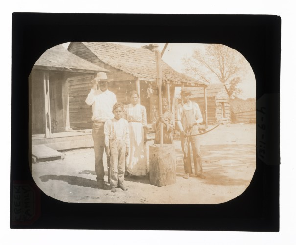 Black-and-white glass lantern slide of Creek family, girl posing with mortar and pestle, boy posing with bow and arrow.