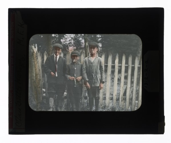 Hand-colored glass lantern slide of three Huron boys, in the attire of the day, smoking by a fence, Ontario, Canada.